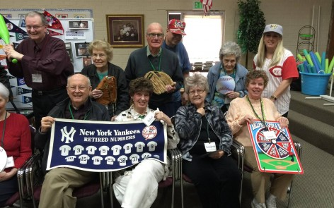 Aspen Senior Center participants holding a baseball chart and memorabilia